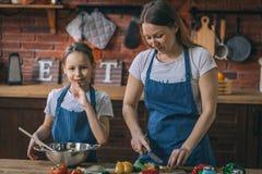 Mädchen und Mutter, die zusammen Salat kochen stockfoto
