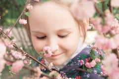 Mädchen und rosafarbene Blumen Stockbild
