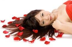 Mädchen und Rosen-Blumenblätter Stockfotos