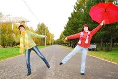 Mädchen und rote Regenschirme im Herbst parken. lizenzfreies stockfoto