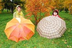 Mädchen und rote Regenschirme im Herbst parken. lizenzfreie stockfotografie