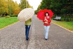 Mädchen und rote Regenschirme im Herbst parken. stockfotos