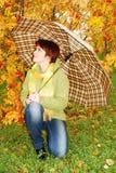 Mädchen und roter Regenschirm im Herbst parken. lizenzfreie stockbilder
