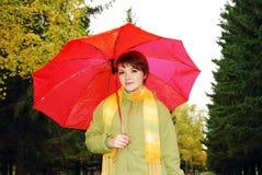 Mädchen und roter Regenschirm im Herbstpark. stockfotos