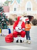 Mädchen und Santa Claus With Wish Letter Stockfoto
