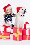 Mädchen und weißer Hund sitzen mit Geschenken Stockbild