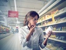 Mädchen ungewiß am Supermarkt lizenzfreie stockbilder