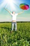 Mädchen unter blauem Himmel mit Regenschirm Stockfoto