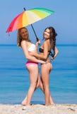 Mädchen unter dem Regenbogenregenschirm Stockfoto