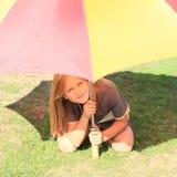 Mädchen unter dem roten und gelben Regenschirm Lizenzfreie Stockbilder