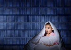 Mädchen unter den Abdeckungen mit einer Taschenlampe Lizenzfreie Stockfotos
