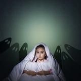 Mädchen unter den Abdeckungen mit einer Taschenlampe Stockbilder