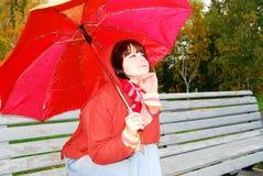 Mädchen unter einem Regenschirm auf einer alten Bank. stockfoto
