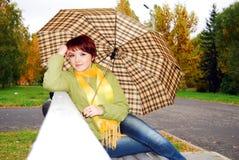 Mädchen unter einem Regenschirm auf einer alten Bank. stockbild