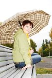 Mädchen unter einem Regenschirm auf einer alten Bank. lizenzfreies stockbild