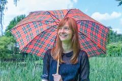 Mädchen unter Regenschirm mit Regen in der Natur Stockfotografie
