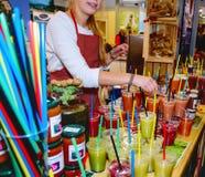 Mädchen verkauft bunte Frucht Smoothies Gesundes Nahrungsmittelkonzept Lizenzfreie Stockfotos