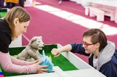 Mädchen verständigt sich mit automatischen Spielwaren an einer Ausstellung in einem Einkaufszentrum Lizenzfreie Stockfotos
