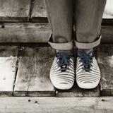 Mädchen versteckt sich im Hemd eines Mannes Weibliche Beine in den Jeans und in gestreiftem Sn Lizenzfreie Stockfotografie
