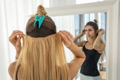 Mädchen versucht auf blonden Strängen des falschen Haares auf Clipn stockfotografie