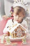 Mädchen verziert Lebkuchenhaus Stockbild