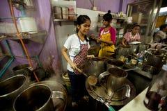 Mädchen vom Lao, der an der Bangkok-Küche arbeitet Stockfotos