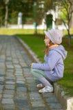 Mädchen-Vorschüler, der auf Stein sitzt Lizenzfreies Stockbild