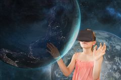 Mädchen in VR-Kopfhörer, der einen Planeten 3D gegen einen blauen Himmel mit Planeten und Sternen berührt Stockbilder