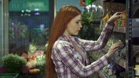 Mädchen wählt Nüsse am Grossmarkt stockfotografie