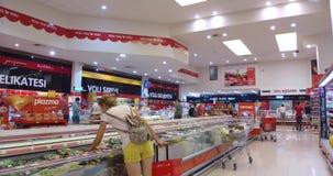 Mädchen wählt Waren und Mahlzeit im Supermarkt Einkauf im Speicher Junge Frau analysiert sorgfältig Produkte in einem Markt stock footage