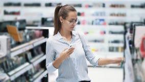 Mädchen wählt Wimperntusche und macht Foto, das sie am Telefon in den Kosmetik kauft, Zeitlupe stock video