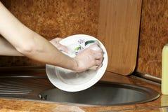 Mädchen wäscht eine Platte Stockbilder