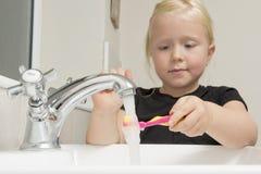 Mädchen-waschende Zahnbürste unter fließendem Wasser in der Badezimmer-Wanne Stockfoto