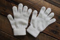 Mädchen-weiße Winter-Handschuhe lokalisiert auf hölzernem Hintergrund Stockfotos