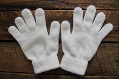 Mädchen-weiße Winter-Handschuhe lokalisiert auf hölzernem Hintergrund Lizenzfreie Stockbilder