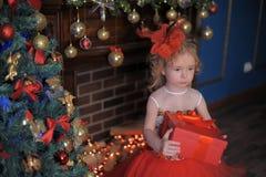 Mädchen am Weihnachtsbaum in einem roten eleganten Kleid mit einem Kasten mit Geschenken in ihren Händen lizenzfreies stockfoto