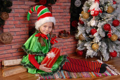 Mädchen-Weihnachtselfe mit Geschenk nahe Weihnachtstannenbaum Stockfoto