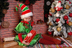 Mädchen-Weihnachtselfe mit Geschenk nahe Weihnachtstannenbaum Lizenzfreie Stockfotos