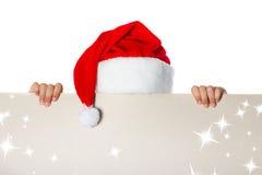 Mädchen in Weihnachtsmann-Hut, der ein Plakat hält Stockfotografie