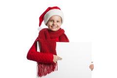 Mädchen in Weihnachtsmann-Hut, der ein Plakat hält Stockfotos