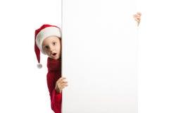 Mädchen in Weihnachtsmann-Hut, der ein Plakat hält Stockbild