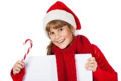 Mädchen in Weihnachtsmann-Hut, der ein Plakat hält Lizenzfreies Stockfoto