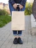 Mädchen, welches das ökologische Einkaufen mit Papiertüte in den Händen hält Stockfotografie