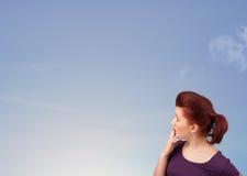 Mädchen, welches das blauer Himmel copyspace betrachtet Stockfoto