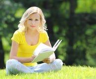 Mädchen, welches das Buch liest. Blonde schöne junge Frau mit dem Buch, das auf dem Gras sitzt. Im Freien. Sonniger Tag. Betrachte Stockbilder