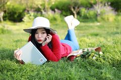 Mädchen, welches das Buch liest schöne junge Frau mit dem Buch, das auf dem Gras liegt outdoor Sonniger Tag lizenzfreie stockfotos