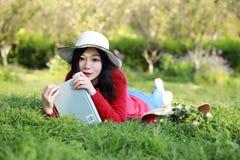 Mädchen, welches das Buch liest schöne junge Frau mit dem Buch, das auf dem Gras liegt outdoor Sonniger Tag lizenzfreie stockfotografie