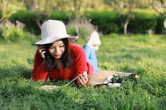 Mädchen, welches das Buch liest schöne junge Frau mit dem Buch, das auf dem Gras liegt outdoor Sonniger Tag lizenzfreie stockbilder