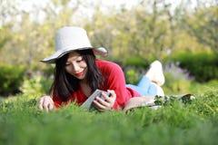 Mädchen, welches das Buch liest schöne junge Frau mit dem Buch, das auf dem Gras liegt outdoor Sonniger Tag lizenzfreies stockbild