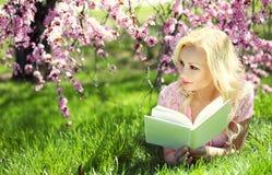 Mädchen, welches das Buch unter Cherry Blossom liest. Blond Lizenzfreie Stockfotografie